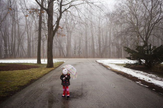 Girl with umbrella walking on road at forest during winter