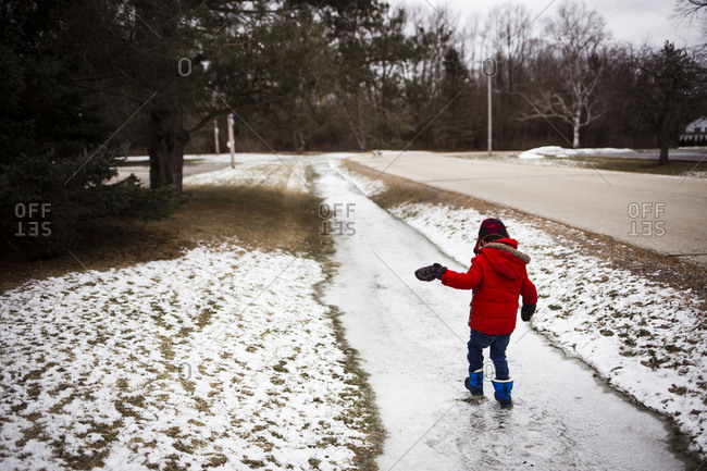 Rear view of boy walking on snow covered footpath