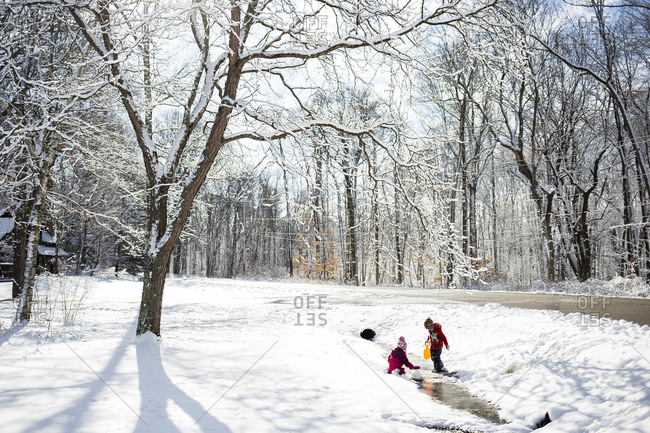 Siblings playing on snow covered field