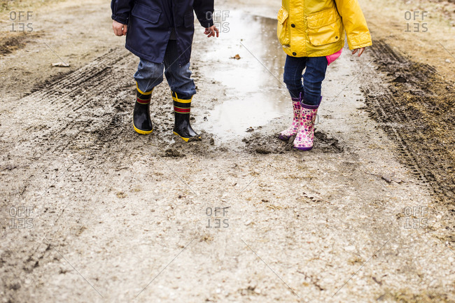 Low section of siblings playing in muddy puddle