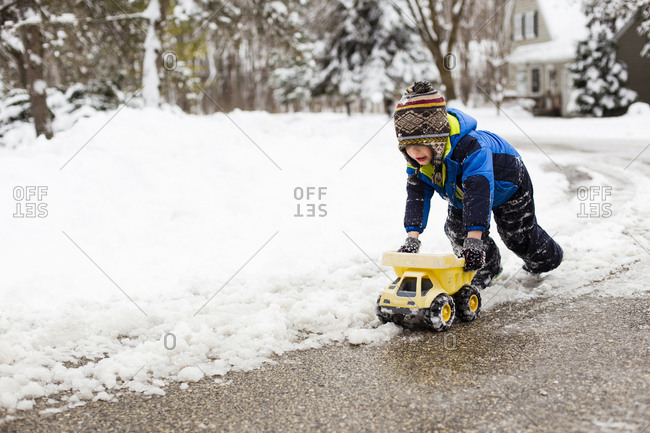 Cute boy playing with toy truck on snow covered road