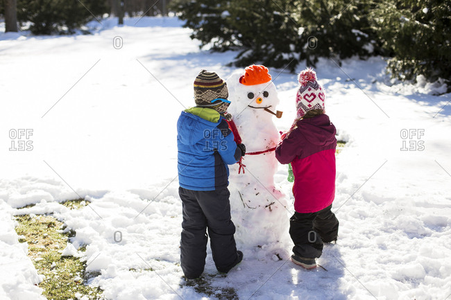 Rear view of siblings making snowman while standing on snow covered field