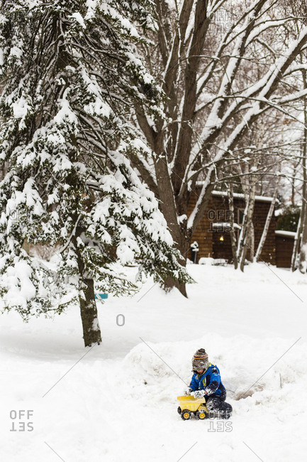 High angle view of boy playing with toy truck on snow covered field