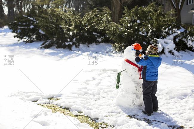 Boy making snowman on snowy field