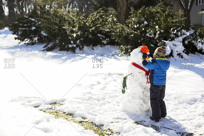 Boy making snowman on snowy field