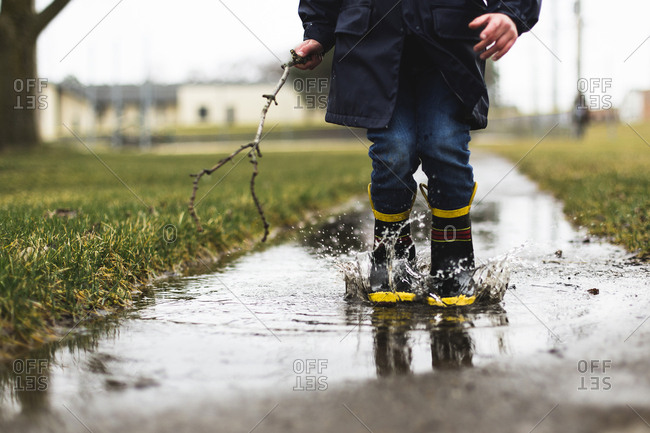 Low section of boy holding stick while jumping in puddle