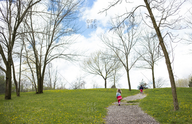 Rear view of siblings walking on footpath against cloudy sky at park