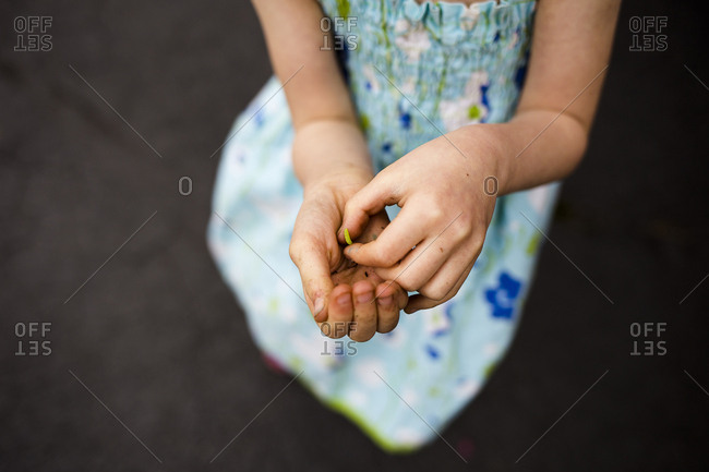 Midsection of girl holding caterpillar while crouching on footpath