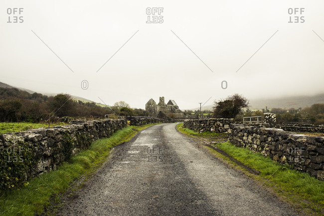 Empty road amidst stone wall against sky during foggy weather