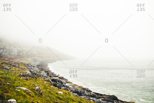 Scenic view of rocky beach against sky during foggy weather