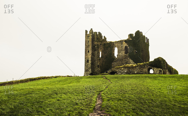 Ballycarbery castle on grassy hill against clear sky