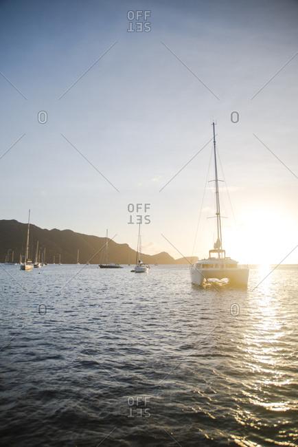 Sailboats sailing in sea against sky during sunrise