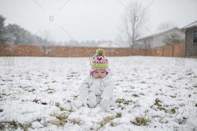 Full length of baby girl sitting on snow covered field against sky