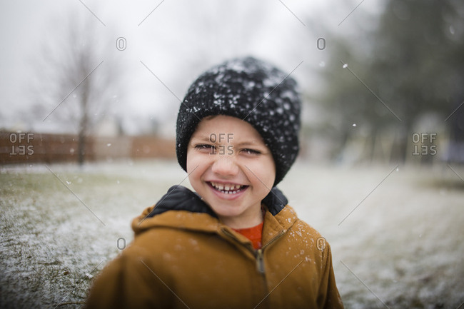 Portrait of happy boy standing on field during winter