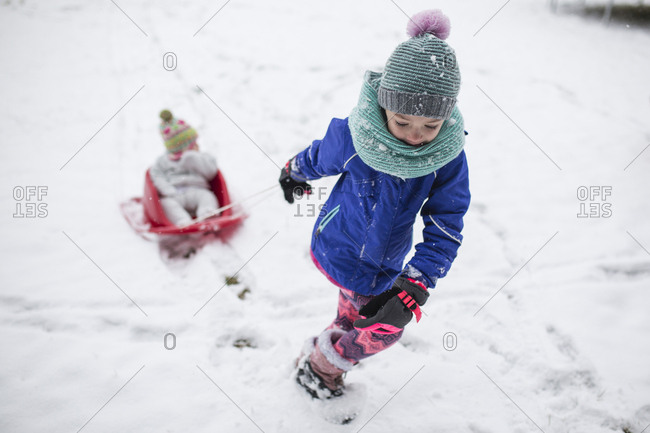 Girl pulling sister sitting in sled on snow covered field