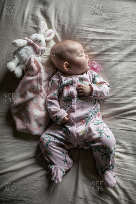 Overhead view of baby girl sleeping on bed at home