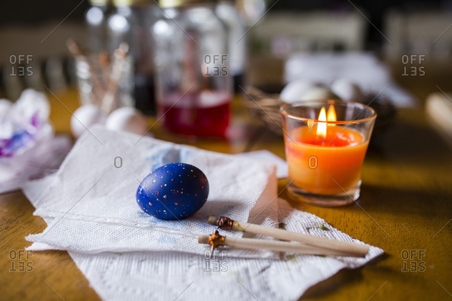 Easter egg with sticks and tissue papers by candle on wooden table