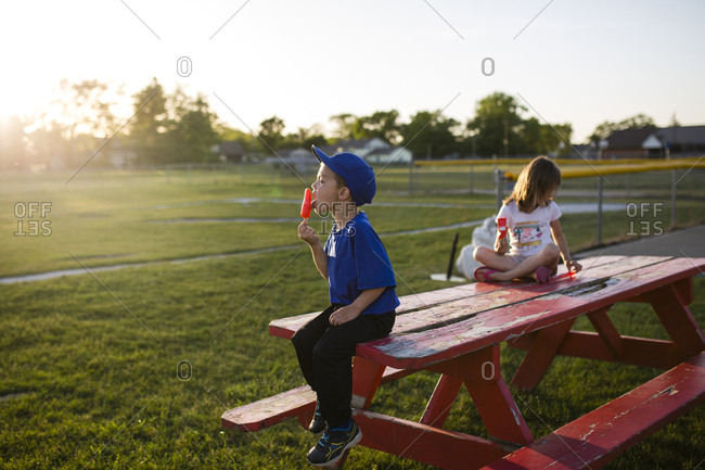 Siblings eating flavored ice while sitting on picnic bench at park
