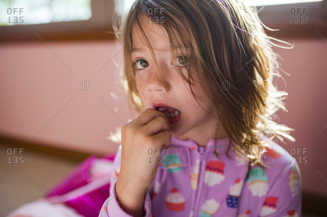 Portrait of girl touching tooth at home