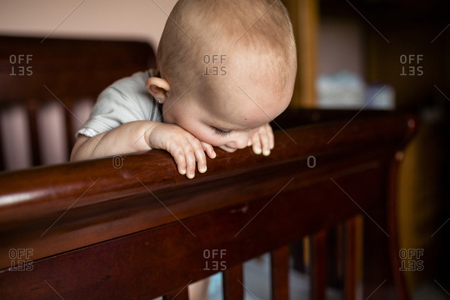 Baby girl biting wooden crib at home