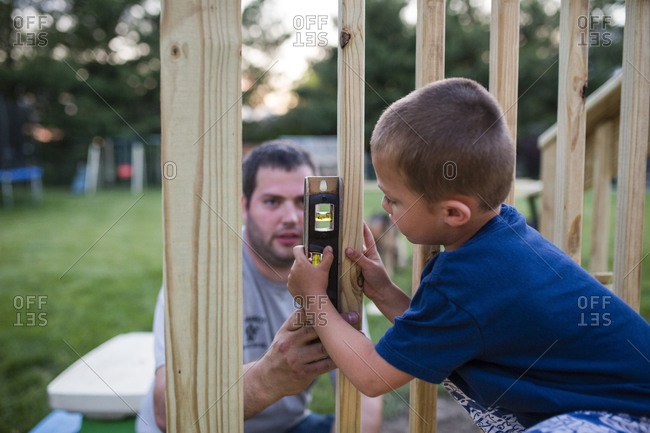 Father teaching son to use spirit level on wooden frame at yard