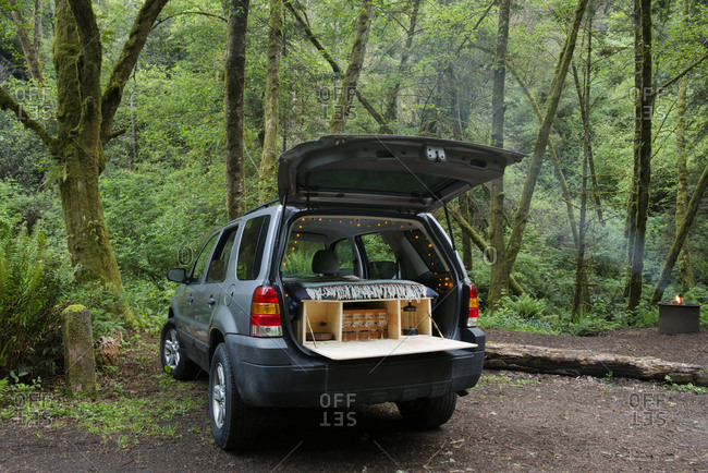 Sports utility vehicle parked at campsite in forest