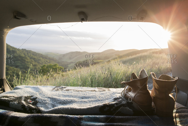 Hiking boots and blanket in sports utility vehicle with hills in background