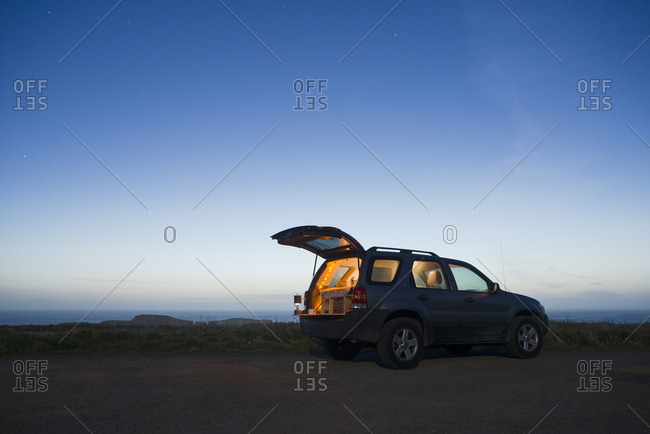 Sports utility vehicle parked on field against clear sky during dusk