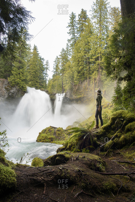 Side view of female hiker looking at waterfall while standing on mossy rock