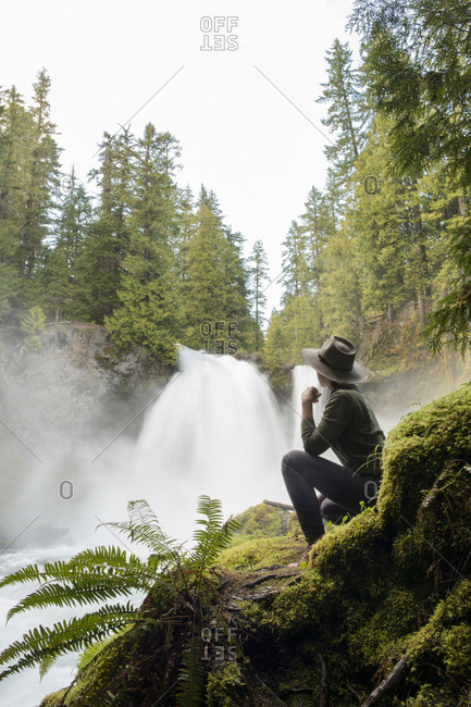Side view of female hiker looking at waterfall while sitting on mossy rock