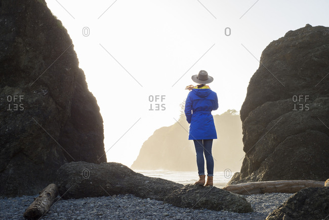 Rear view of female hiker standing at Ruby Beach against clear sky