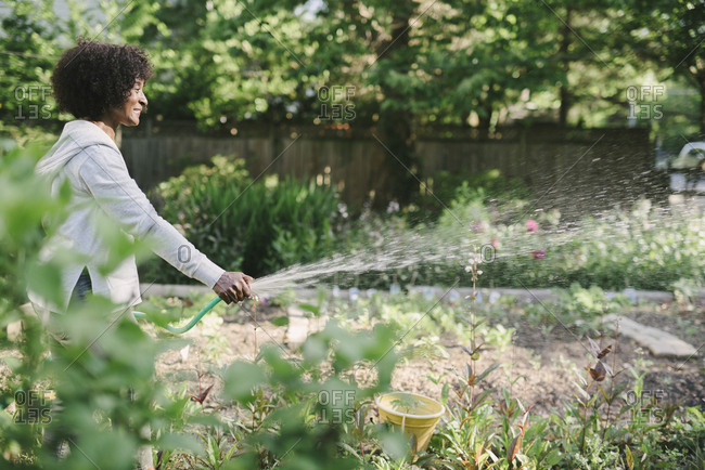 Side view of mature woman watering plants in garden