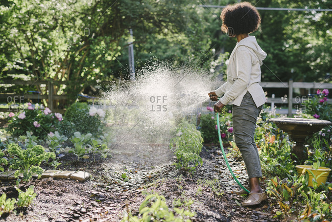 Side view of mature woman watering plants in yard