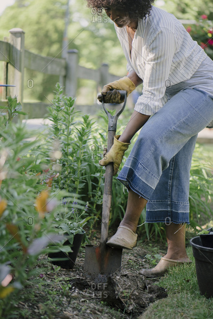 Woman shoveling soil in garden