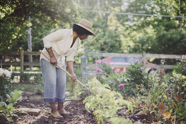 Woman using gardening fork in garden