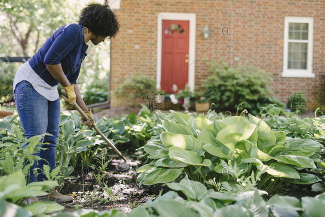 Woman using gardening fork while working in yard
