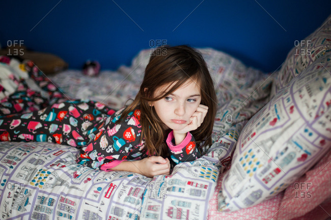 Thoughtful girl lying on bed at home