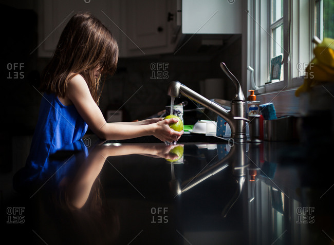 Side view of girl washing granny smith apple at kitchen sink