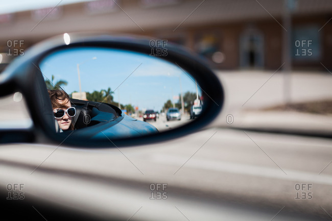 Girl reflecting in side-view mirror of car