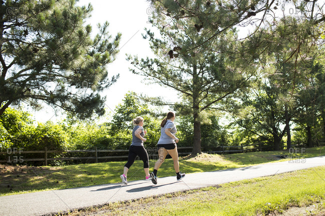 Full length of mother and daughter jogging on footpath at park during sunny day