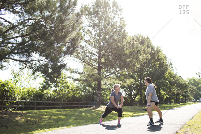Full length of mother and daughter stretching legs while exercising on footpath at park