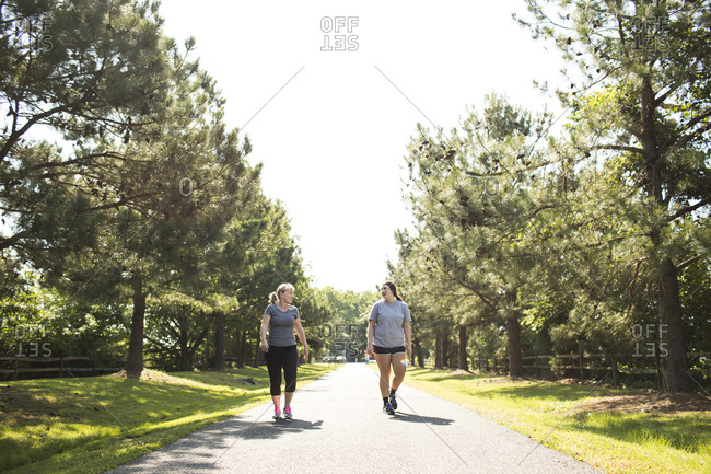Mother and daughter in sportswear walking on footpath at park during sunny day
