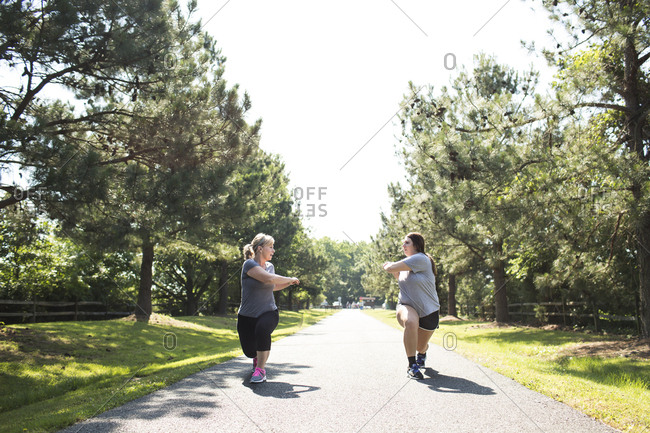 Mother and daughter stretching arms and legs on footpath at park during sunny day