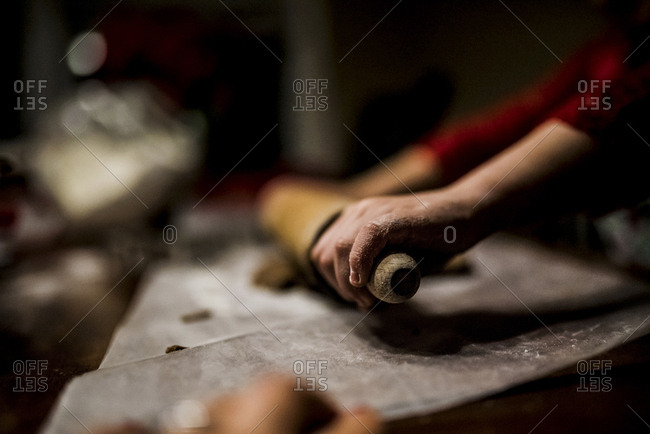 Cropped image of girl rolling dough in kitchen