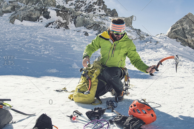 Male hiker with ice climbing equipment crouching on mountain