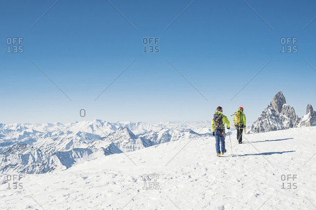 Rear view of hikers walking on snow covered mountain against clear blue sky