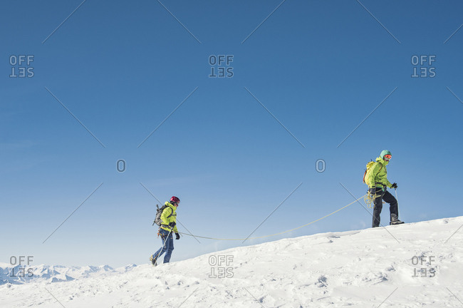 Side view of hikers walking on snow covered mountain against clear blue sky