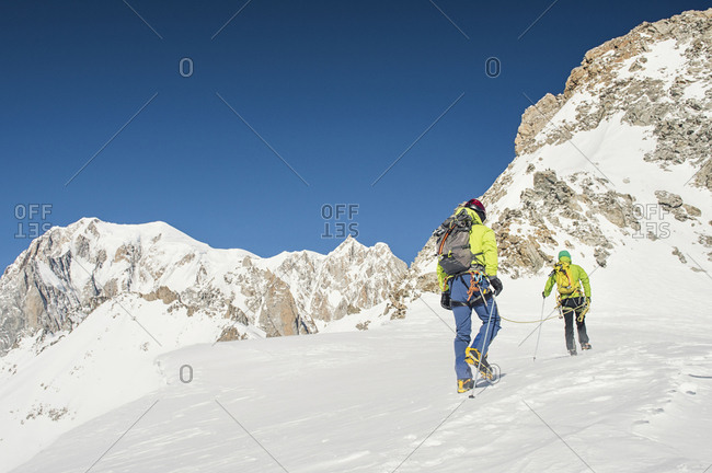 Rear view of hikers with backpacks climbing mountain against clear blue sky during sunny day