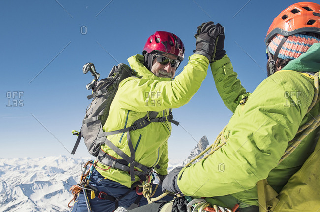 Hikers giving high-five while climbing mountain against clear blue sky