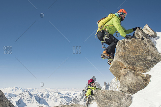 Hikers climbing mountain against clear blue sky during winter on sunny day